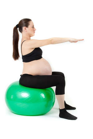 Beautiful pregnant woman sitting with exercise bal  Isolated on white background photo