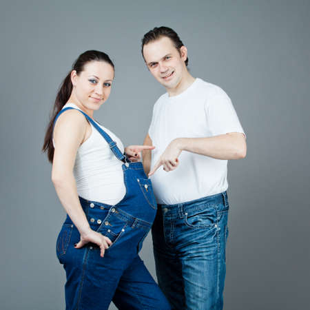 A man and a pregnant woman, the couple posing on a gray background Stock Photo - 15616196