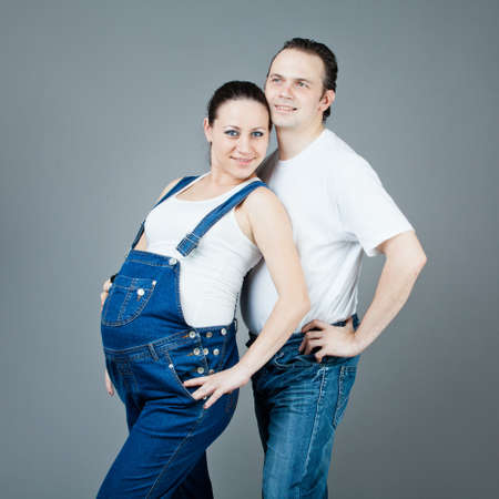 A man and a pregnant woman, the couple posing on a gray background Stock Photo - 15616187