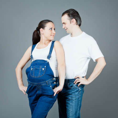 A man and a pregnant woman, the couple posing on a gray background Stock Photo - 15616190