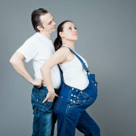 A man and a pregnant woman, the couple posing on a gray background Stock Photo - 15616188