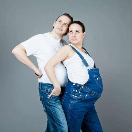 A man and a pregnant woman, the couple posing on a gray background Stock Photo - 15616191