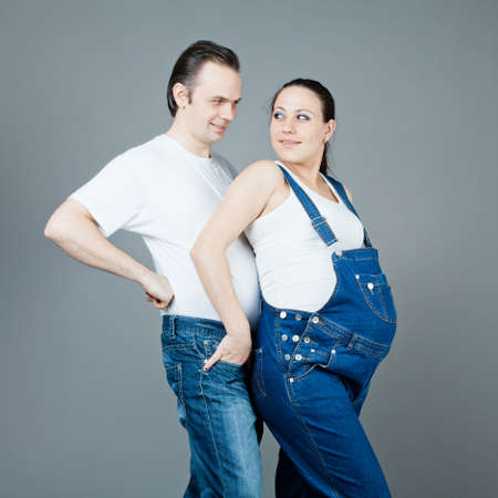 A man and a pregnant woman, the couple posing on a gray background Stock Photo - 15616189