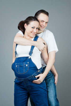 A man and a pregnant woman, the couple posing on a gray background Stock Photo - 15616184