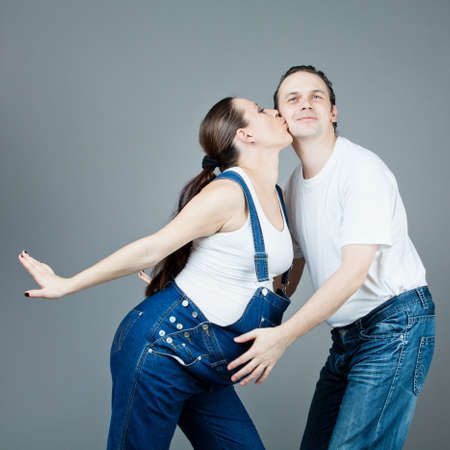 A man and a pregnant woman, the couple posing on a gray background  photo