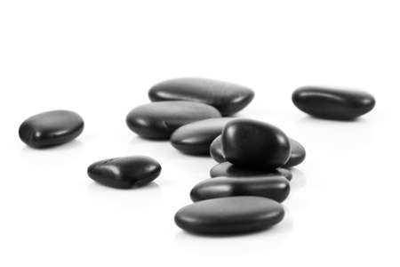 Black massage stones stacked, isolated  photo