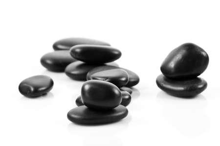 Black massage stones stacked, isolated  photo