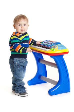 niño y el teclado en el fondo blanco. bebé gracioso. joven DJ