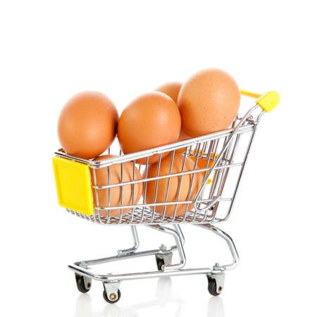 isolaten: Eggs in the shopping cart isolaten in white. Brown eggs in the basket