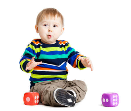 baby is playing with  toys over white background  Funny little kid playing with cup toys photo