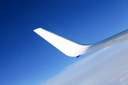 Airplane wing. Wing of an airplane flying above the clouds. photo