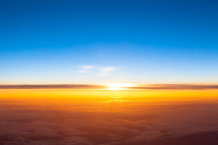 Dramatic sunset. View of sunset above clouds from airplane window Stock Photo