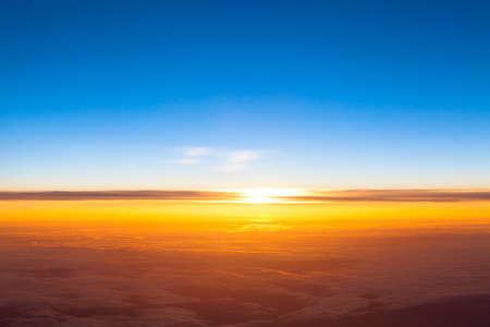 Dramatische zonsondergang. Uitzicht op de zonsondergang boven de wolken uit vliegtuig venster