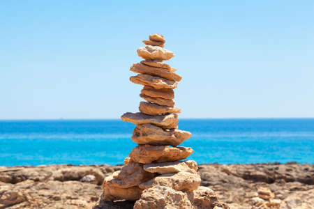 Balanced stones, pebbles stacks against blue sea. photo