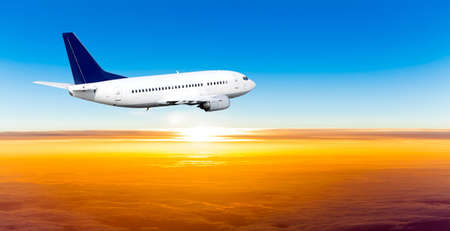 Airplane in the sky at sunset. A passenger plane in the sky Stock Photo