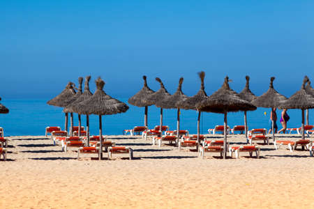 beach scenery with parasol and deck chairs. umbrella and deck chairs photo