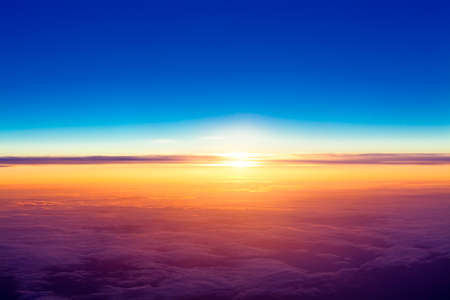 airplane window: sunset with a height of 10 000 km  Dramatic sunset  View of sunset above clouds from airplane window Stock Photo