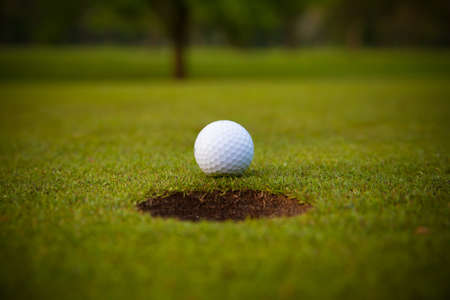 golf ball on lip of cup. photo