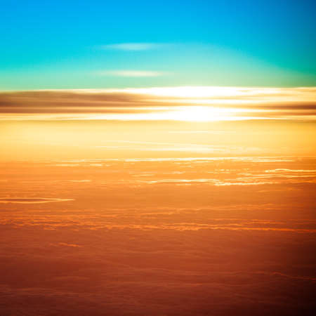 sunset with a height of 10 000 km. Dramatic sunset. View of sunset above clouds from airplane window photo