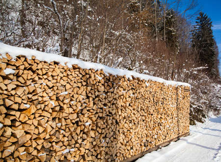Firewood stacked in winter. Wood pile with snow stacked for firewood Stock Photo - 22135761