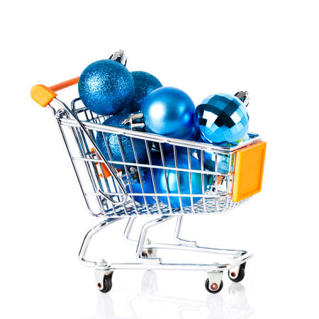 Shopping cart full of christmas balls isolated on white background photo