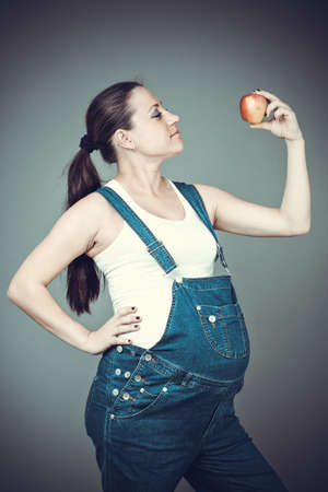 Pregnant beautiful girl in denim overalls. Pregnant woman posing on a gray background photo