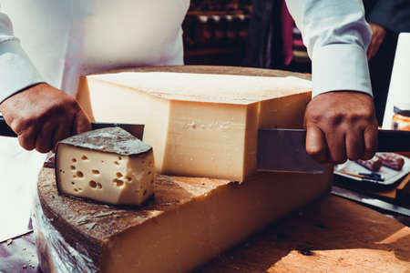 Worker slicing the cheese. Close up of Cutting cheese. Standard-Bild