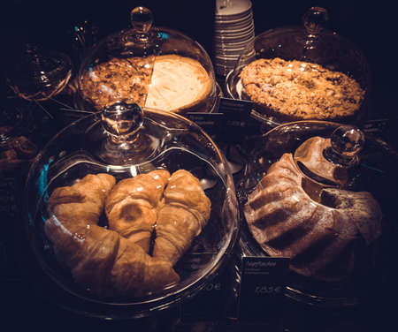 Cakes under bell-glass on display. bakery glass case full of different pieces of cakes photo