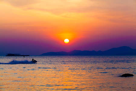 jetski: the jetski above the water at sunset.  Silhouette of people on a jet ski running pass the romantic sunset in the sea.