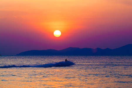 jet skier: the jetski above the water at sunset.  Silhouette of people on a jet ski running pass the romantic sunset in the sea.