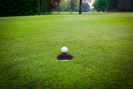 golf course: golf ball on lip of cup.  Golf ball and hole