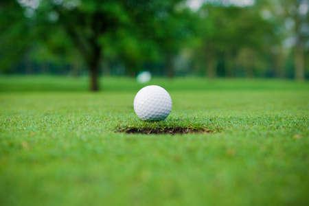 golfbal op de lip van de beker. Golfbal en gat