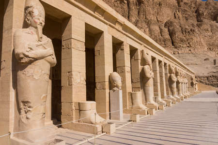 obelisk stone: The temple of Hatshepsut near Luxor in Egypt.  Statues of Queen Hatshepsut as Osiris, the god of the dead, at her temple in Luxor Stock Photo