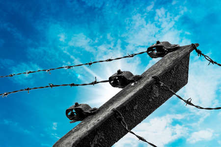 keepout: Barbed wire on blue sky Stock Photo