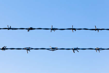 prison system: Barbed wire and blue sky Stock Photo