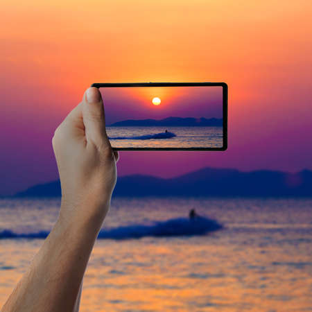 jetski: the jetski above the water at sunset.  Taking photo on smartphone