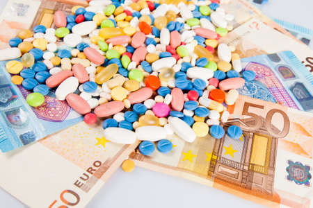 high cost of healthcare: pills on money.  medicine tablets on money