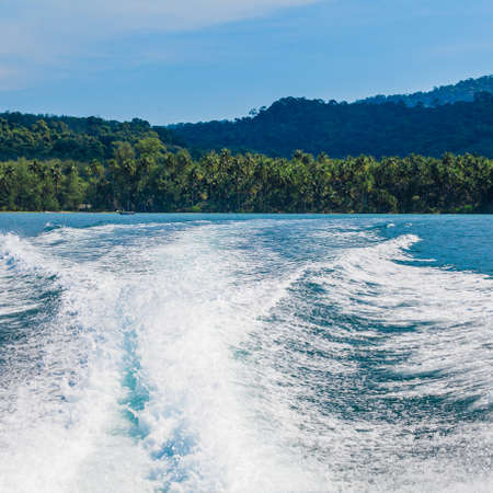 Water stream after speed boat.  Trail on water surface behind of fast moving motor boat. Waves on blue sea