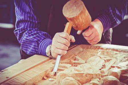 mani dell'artigiano ritagliarsi un bassorilievo con una sgorbia. mani Artigiano di lavoro. Lavoro di artista