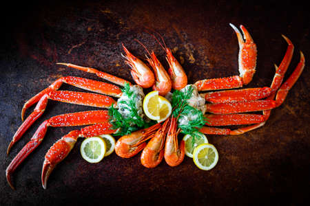 Crab legs with lemon and shrimps Stock Photo
