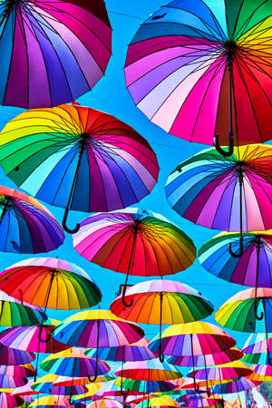 Rainbow umbrella on sky background. Many colorful umbrellas. umbrella street decoration