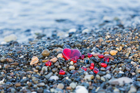 Pebble stones on the beach. Background of sea stones.  stones with hearts. Red heart of the stones Reklamní fotografie
