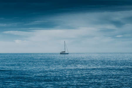 Sailing boat on Blue sea with heavy storm clouds. Sailing yacht race