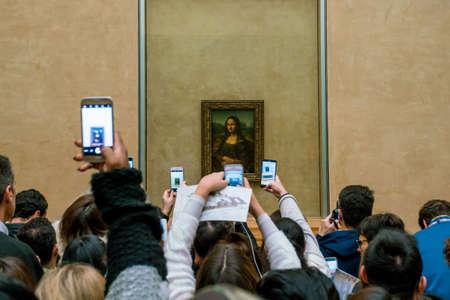 PARIS, FRANCE - FEBRUARY 15, 2018: Visitors take photo of Leonardo DaVincis Mona Lisa at the Louvre Museum