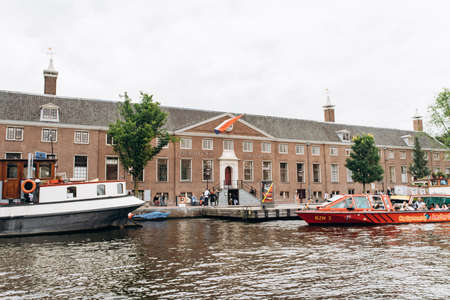 Amsterdam, Netherlands - September 5, 2017: Outside view of the entrance tot the Hermitage Amsterdam Museum, with people passing by and the Dutch flag flying.