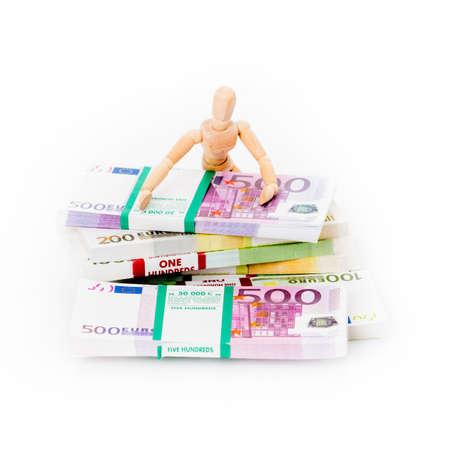 Wooden figurine and euro money Archivio Fotografico