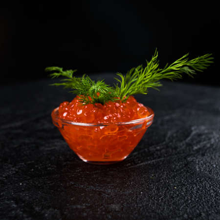 Red Caviar in bowl over black background