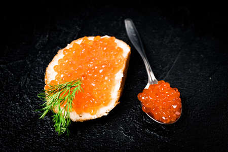 Red caviar with bread on black