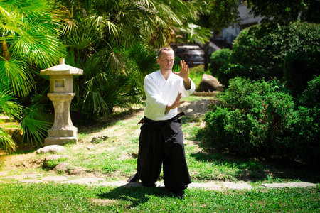Young serious man aikido master in traditional costume Editorial