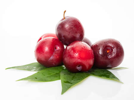 Red  plum with green leaves isolated on white Banco de Imagens